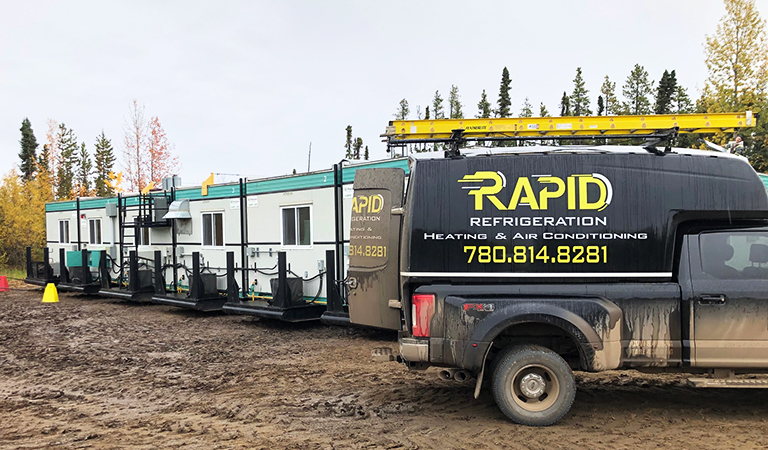 Rapid Refrigeration service truck parked next to trailers on oilfield camp